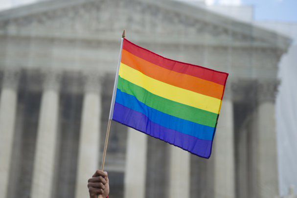 A same-sex marriage supporter waves a rainbow flag in front of the US Supreme Court on March 26, 2013 in Washington, DC, as the Court takes up the issue of gay marriage. The US Supreme Court on Tuesday heard arguments on the emotionally charged issue of gay marriage as it considers arguments that it should make history and extend equal rights to same-sex couples. Waving US and rainbow flags, hundreds of gay marriage supporters braved the cold to rally outside the court along with a smaller group of opponents, some pushing strollers. Some slept outside in hopes of witnessing the historic hearing. AFP PHOTO / Saul LOEB (Photo by Saul LOEB / AFP)        (Photo credit should read SAUL LOEB/AFP/Getty Images)