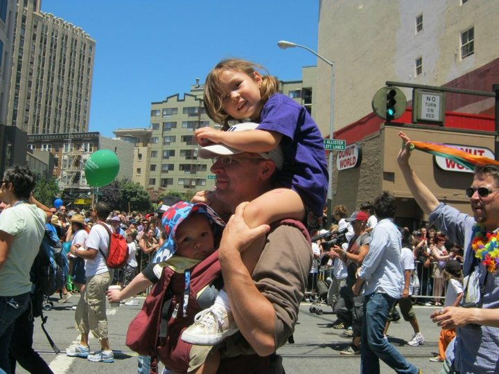 kid on dad's shoulders plus baby in carrier at OFC's contingent in 2010 SF LGBTQ Pride
