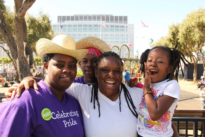 family of 4 all smiles at OFC's Family Garden, 2011 SF LGBTQ Pride