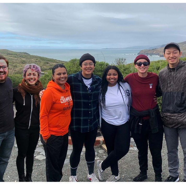7 Programs staff pose smiling on a bluff with Pacific Ocean behind